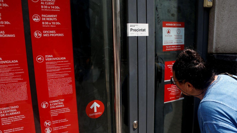 Foto: Una señora se asoma a la puerta de una sucursal. (EFE)