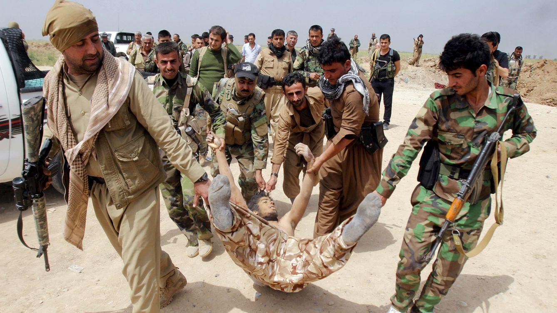 Foto: Kurdos peshmerga arrastran el cadáver de un combatiente del ISIS tras combates en las afueras de Kirkuk. (Reuters)