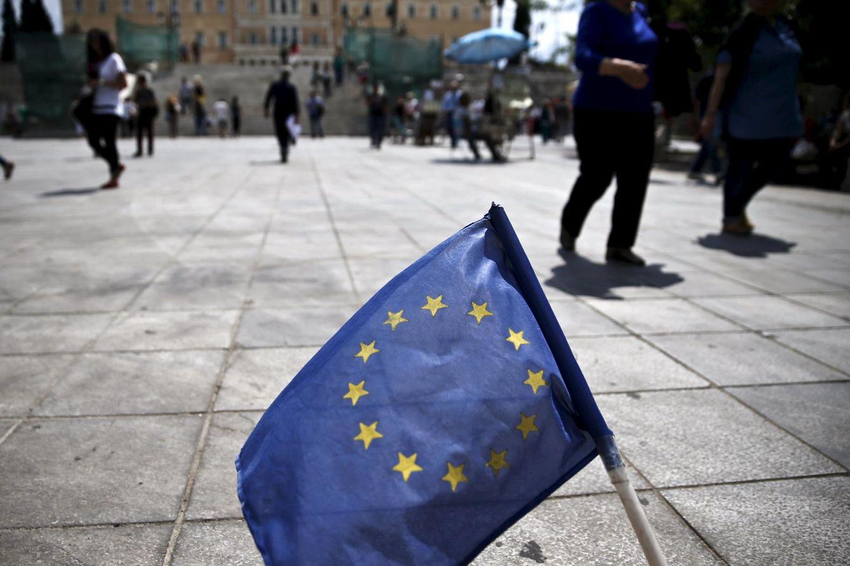Foto: Ciudadanos griegos pasan ante una bandera de la UE en la Plaza Syntagma de Atenas. (Reuters)