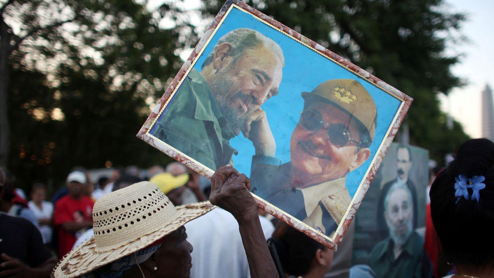 Foto: Una mujer carga un cuadro con los hermanos Fidel y Raúl Castro en La Habana. (Reuters)