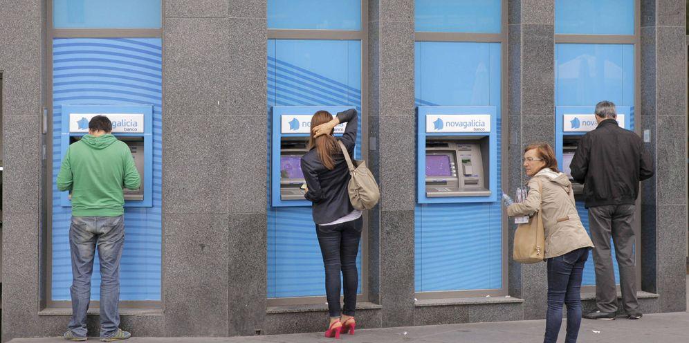 Foto: Usuarios retiran dinero de varios cajeros en una sucursal bancaria. (EFE)