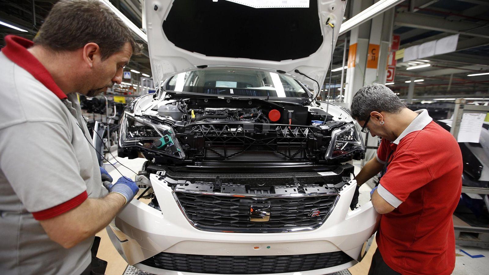 Foto: Dos trabajadores se encargan de colocar la parte delantera de un vehículo Seat en la fábrica de Martorell, Barcelona. (EFE)