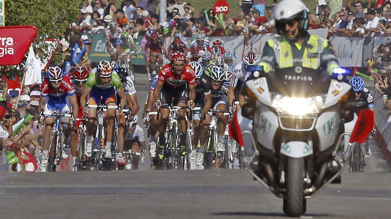 Una moto de la Guardia Civil ante un grupo ciclista en la Vuelta (EFE/José Manuel Vidal).