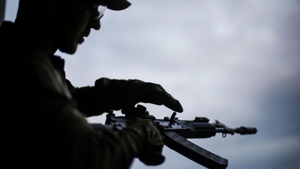 Foto: Un visitante se prepara para disparar un rifle de asalto AK-12 en una presentación de nuevos modelos (EFE)