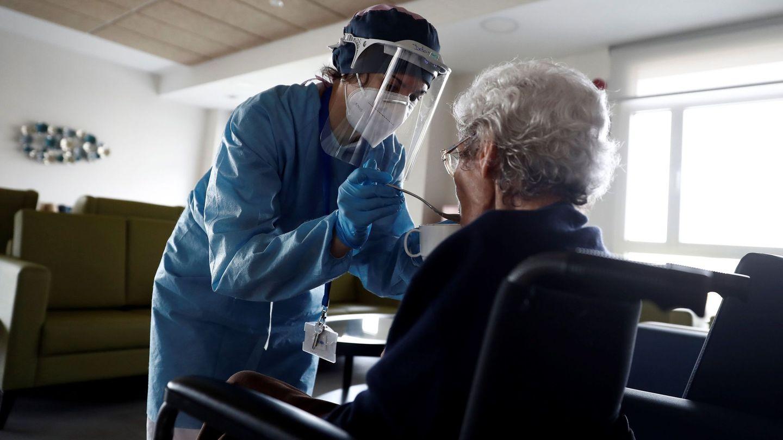 Una cuidadora ayuda a comer a una anciana en la residencia Casablanca, en el barrio madrileño de Villaverde. (EFE)