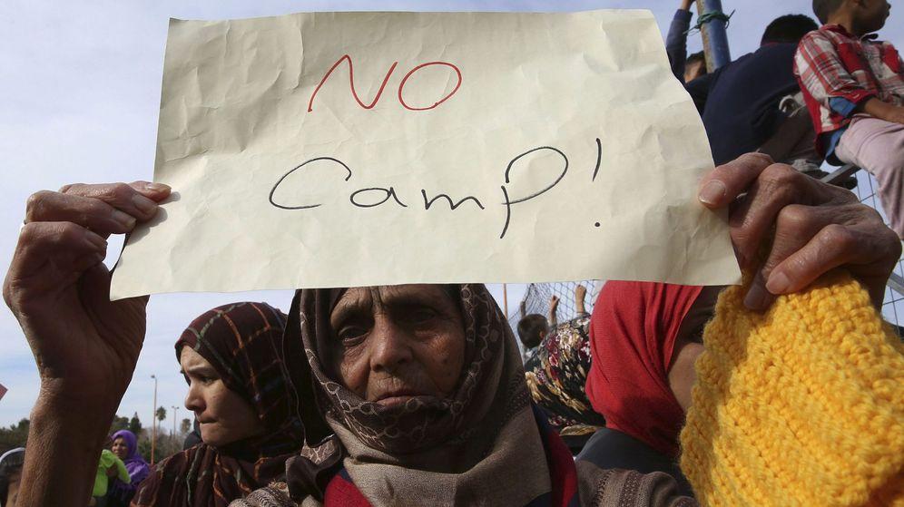Foto: Una mujer sostiene un papel durante la manifestación en contra del estado de los refugiados en un asentamiento de Grecia. (Reuters)