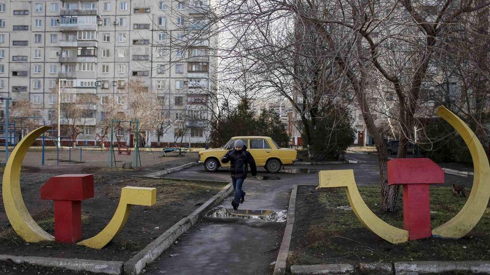 Foto: Un niño juega entre dos esculturas de la hoz y el martillo en un barrio residencial de Mariupol, en el este de Ucrania, en febrero de 2015. (Reuters)