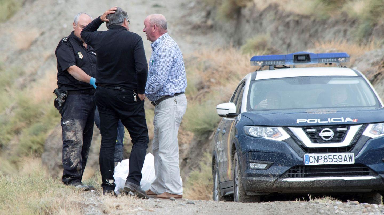 Agentes de la Policía Nacional y varias personas junto al cuerpo sin vida hallado este viernes en el entorno de una rambla. (EFE)