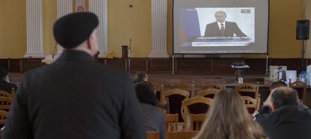 Foto: Varios ucranios, frente a una pantalla en la que se televisa un discurso de Putin. (Reuters)