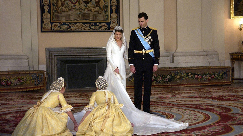 Las damas de honor acondicionan el vestido para la foto oficial. (Getty)