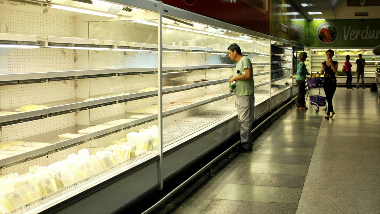 Un venezolano busca productos en un refrigerador en un supermercado en San Cristóbal, Venezuela. (Reuters)