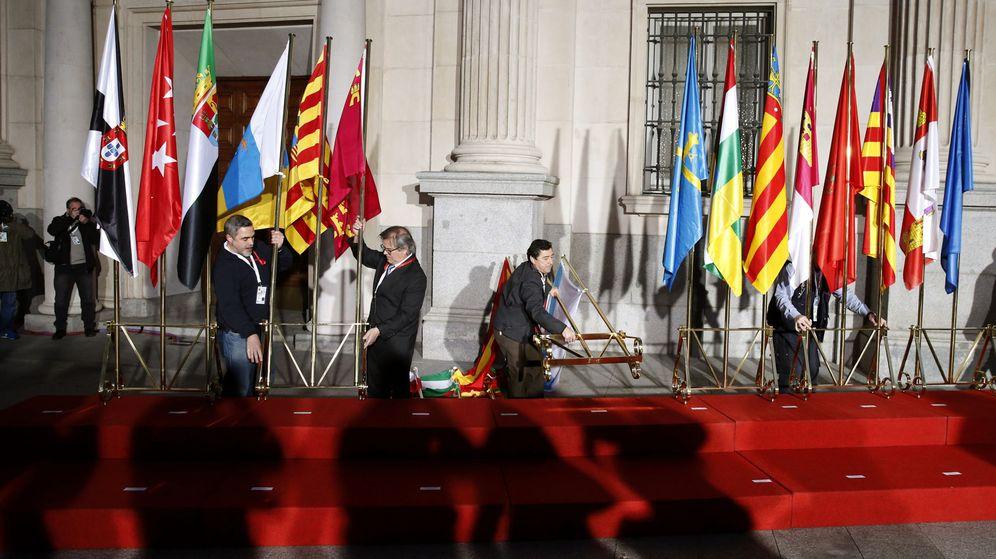 Foto: Unos operarios colocan las banderas autonómicas caídas a consecuencia del viento a las puertas del Senado, coincidiendo con la VI Conferencia de Presidentes. (EFE)