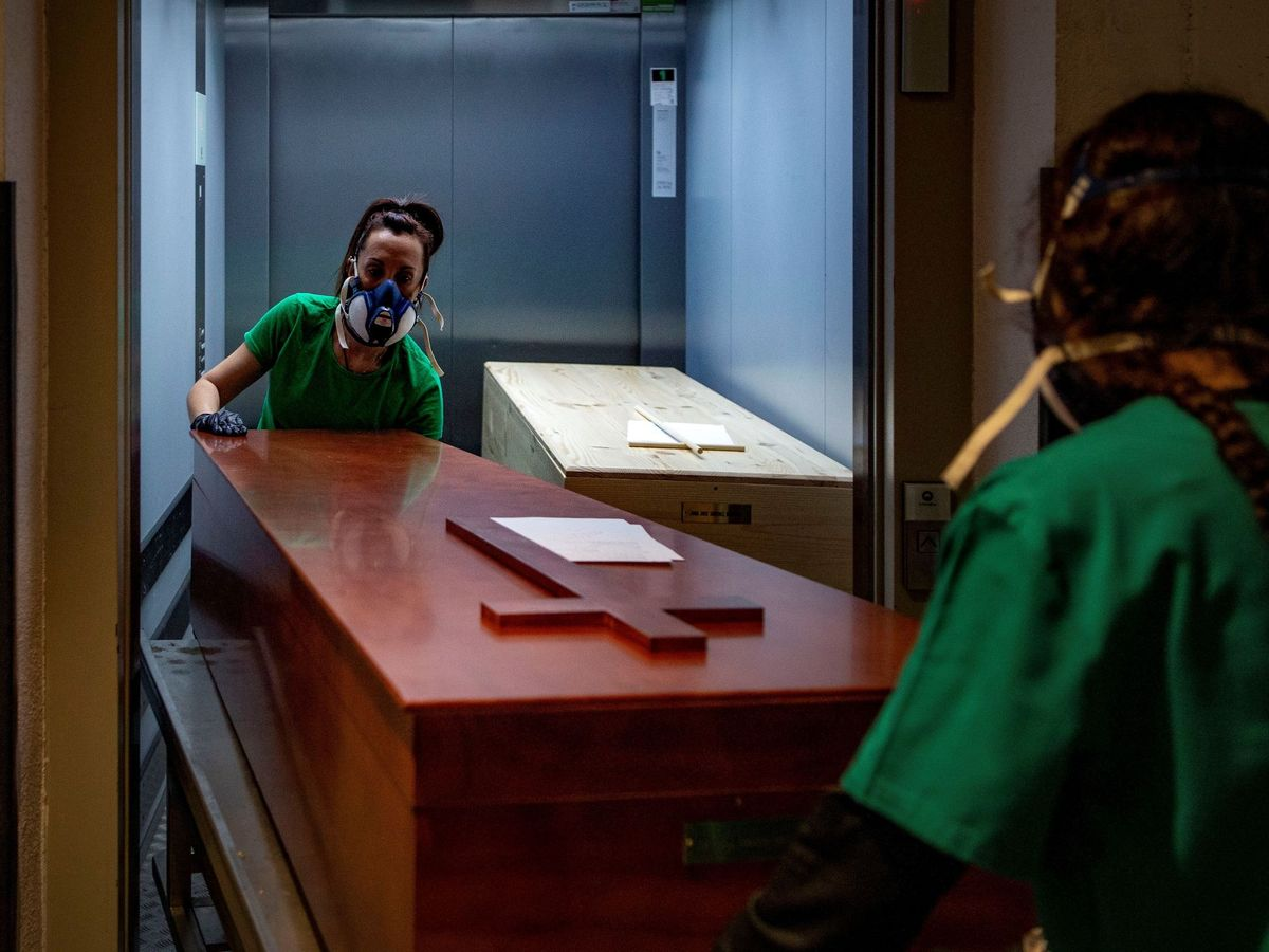 Foto: Dos empleadas de una funeraria, en un tanatorio de Barcelona, en febrero de 2020. (EFE)