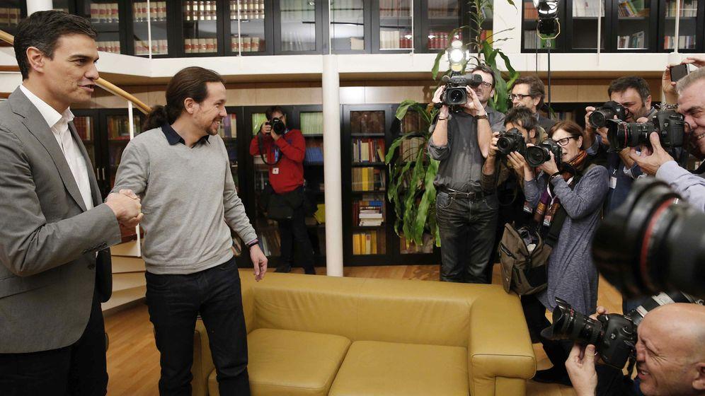 Foto: Pedro Sánchez y Pablo Iglesias se saludan ante las cámaras minutos antes de su reunión en el Congreso el pasado 5 de febrero. (EFE)
