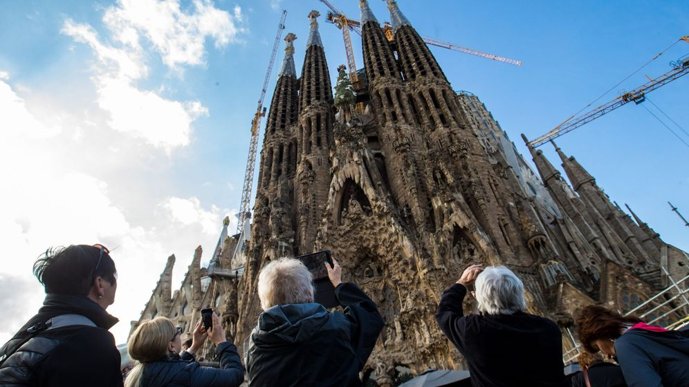 Foto: Un grupo de turistas extranjeros admira la fachada de la Sagrada Familia en Barcelona. (EFE)