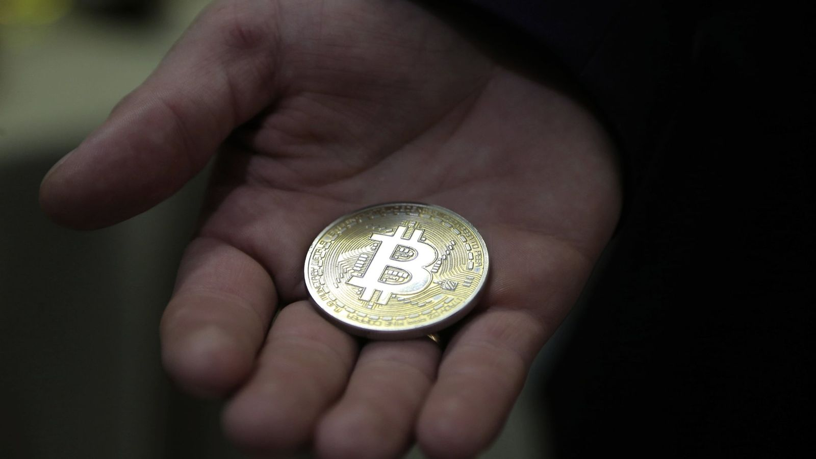 Foto: Fotografía de archivo, del 29 de agosto de 2017, de un hombre que sujeta un bitcoin. (EFE)
