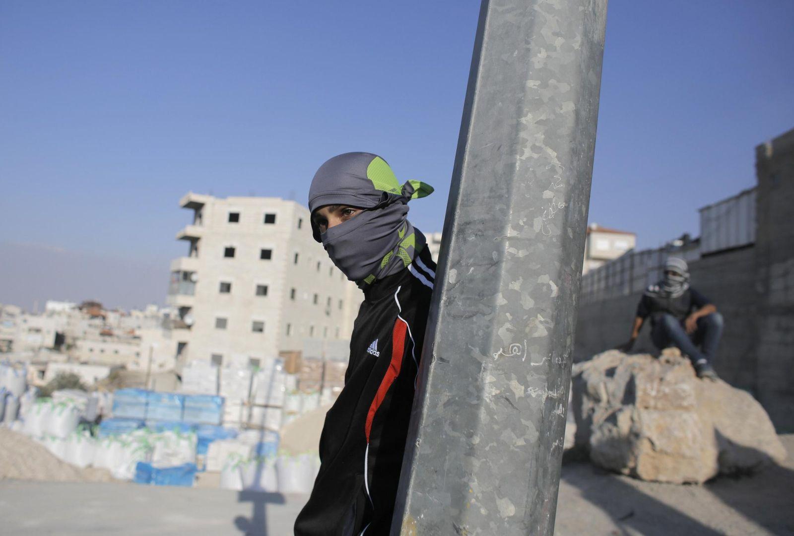 Foto: Un palestino que arroja piedras a la policía israelí se cubre tras un poste durante choques en el barrio de Issawiya. (Reuters)