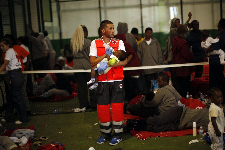 Foto: Un miembro de Cruz Roja alimenta al bebé de una inmigrante africana tras su llegada a Tarifa, el 13 de agosto de 2014 (Reuters).