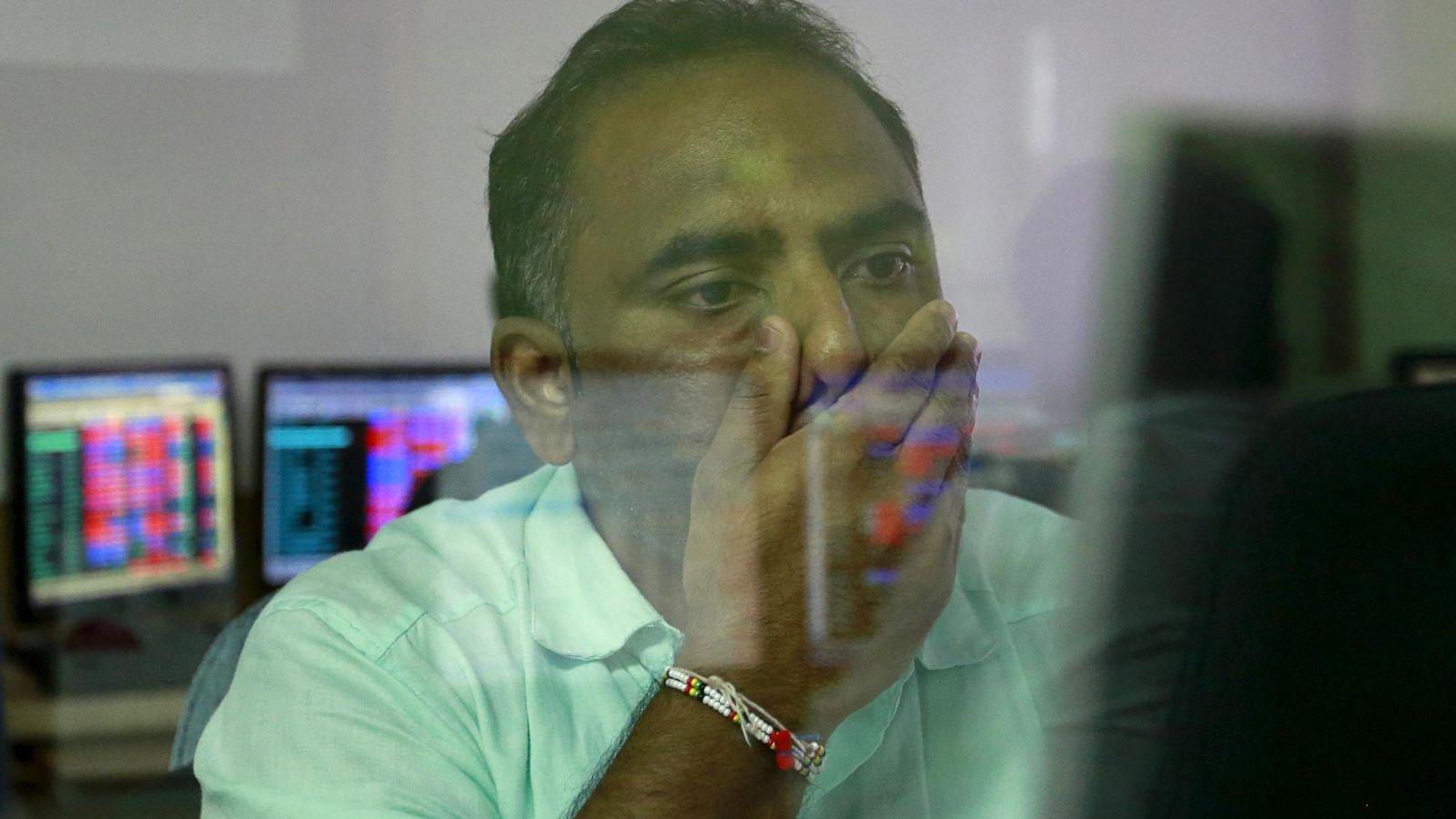 Foto: Un inversor mira con preocupación las pantallas de cotizaciones en India. (EFE)