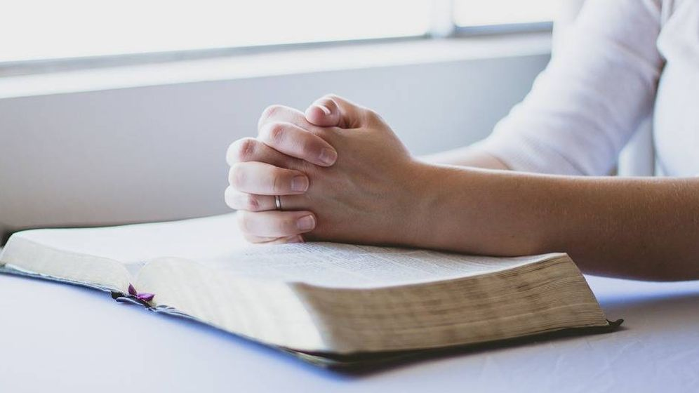 Foto: Una mujer reza sobre una Biblia. Foto: Pixabay.