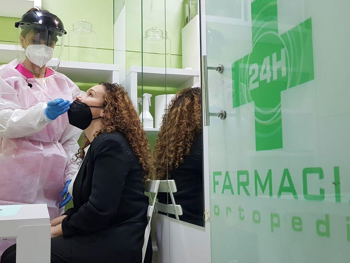 Foto: Una mujer se hace un test de antígenos en una farmacia. (EFE)