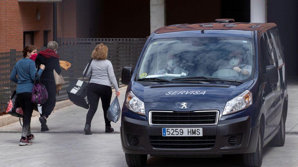 Foto: Trabajadores de una residencia de ancianos de Murcia pasan junto a un furgón fúnebre. (EFE)