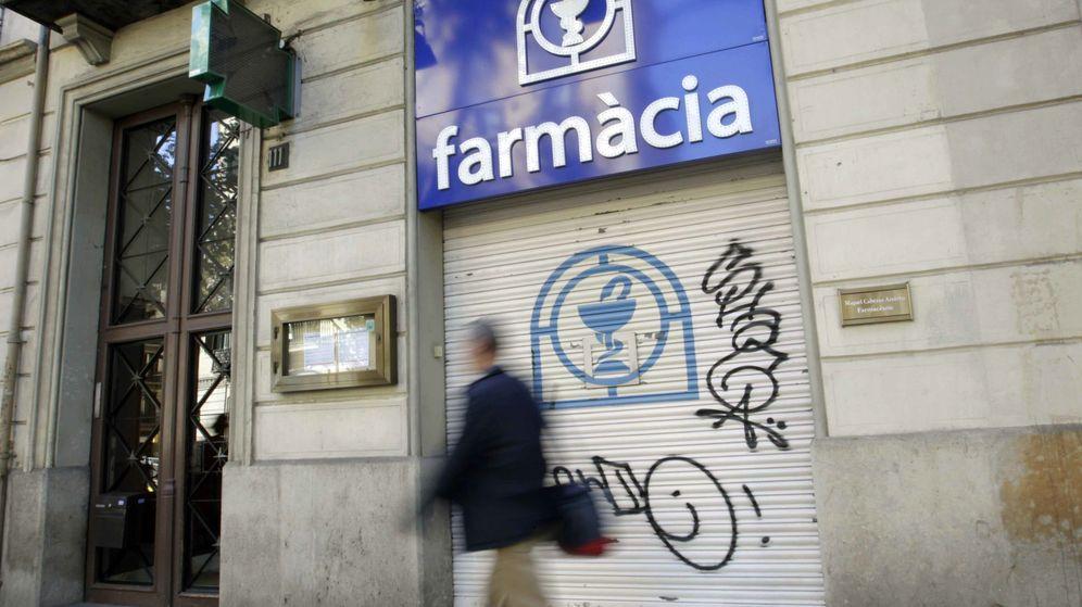 Foto: Una persona camina ante la fachada de una farmacia cerrada en el centro de Barcelona. (Efe)