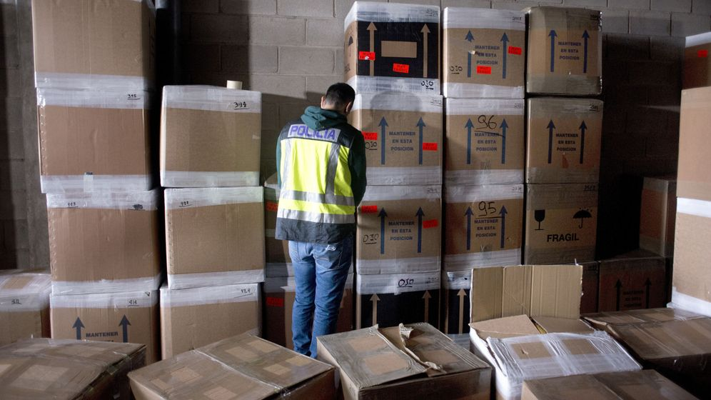 Foto: Un policía inspecciona bienes de afectados por la estafa de una empresa de paquetería. (EFE)