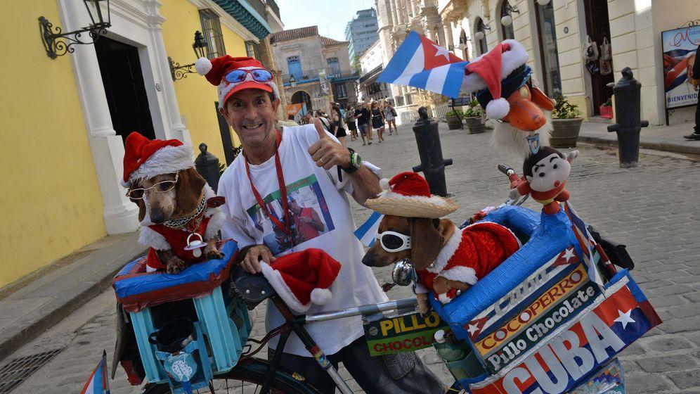 Foto: Un vendedor ambulante, anunciando sus productos con sus perros en La Habana, el 23 de diciembre de 2015. (EFE)