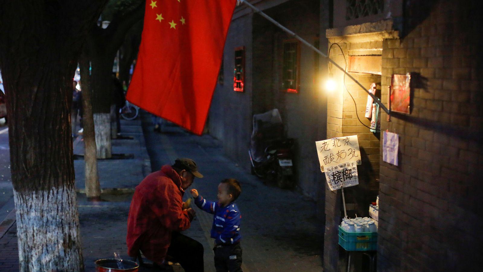 Foto: Un hombre juega con un niño en un callejón en la parte vieja de Pekín, en octubre de 2017. (Reuters)