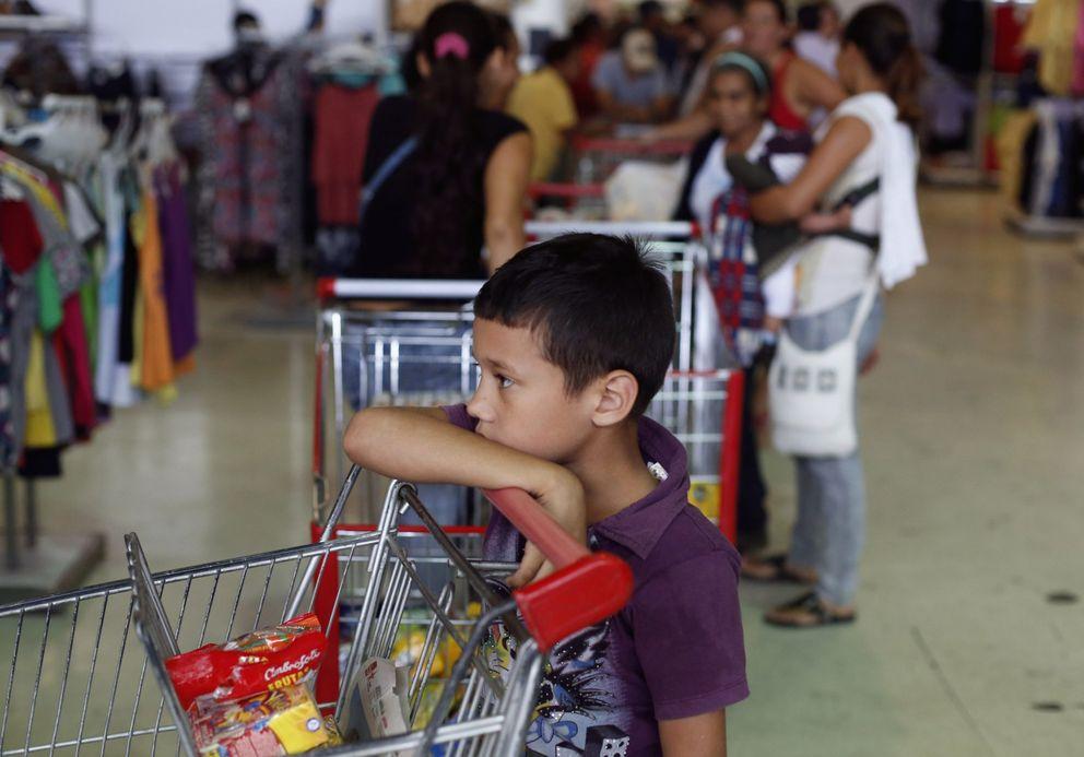 Un niño espera en una cola en un supermercado de Caracas (Reuters).
