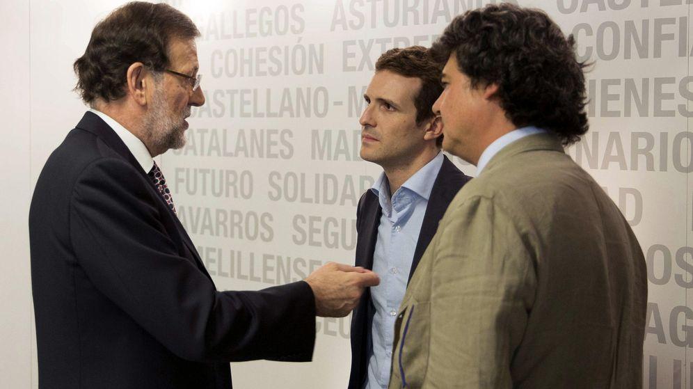 Foto: Mariano Rajoy (i) conversa con el que será vicesecretario de Comunicación, Pablo Casado (2d), y el futuro director de campaña para las elecciones generales, Jorge Moragas (d). (EFE)