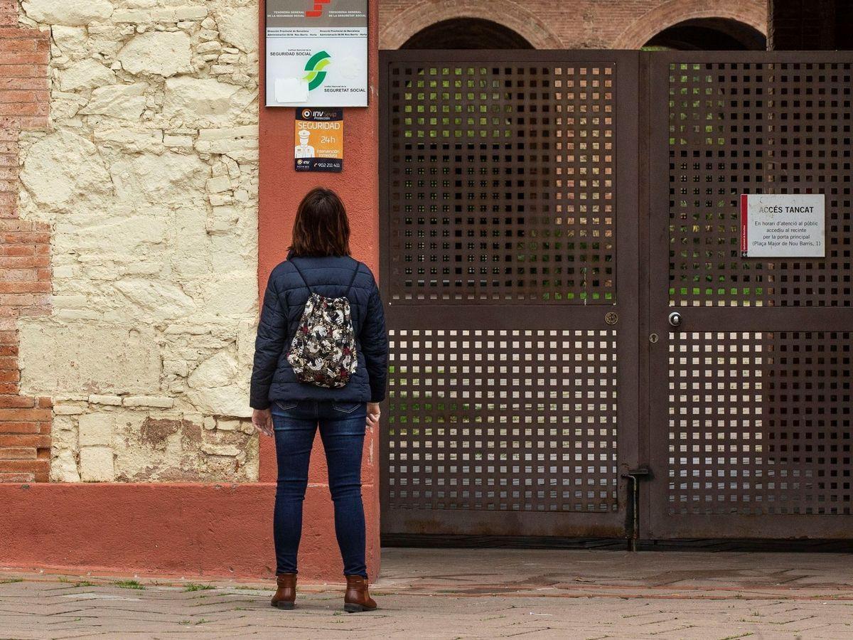Foto: Una mujer mira el carte de una oficina de la Seguridad Social en Barcelona (EFE)