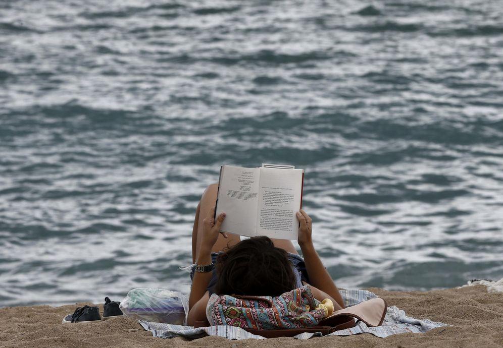 Foto: Una mujer leyendo en la Barceloneta (Efe)
