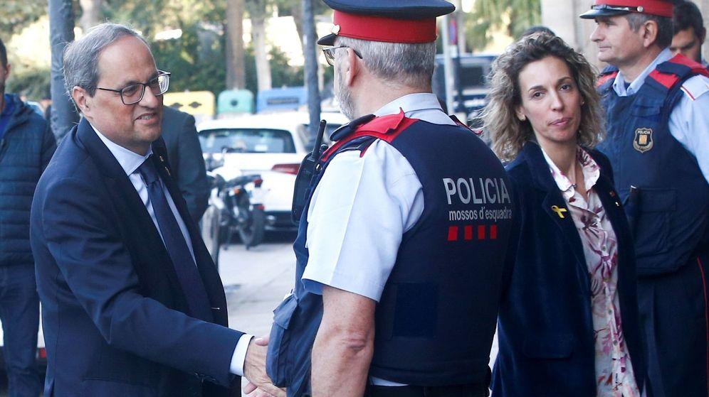 Foto: Quim Torra saluda a un agente de los Mossos en el Parlament. (EFE)