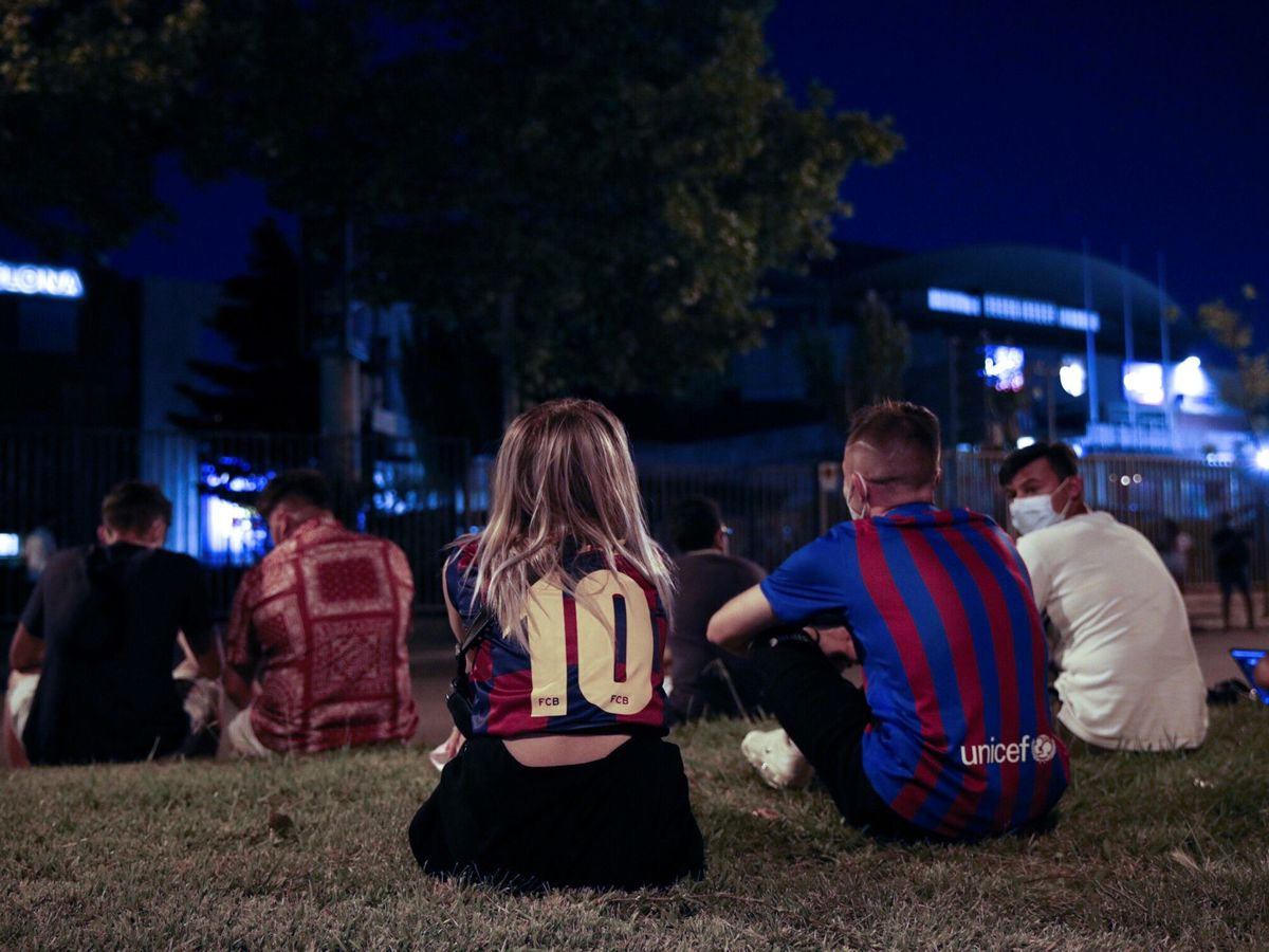 Foto: Aficionados, acampados en las puertas del Camp Nou por la salida de Messi. (EFE)
