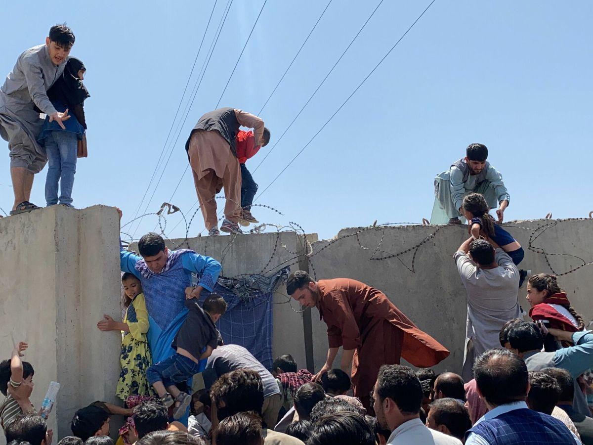 Foto: Ciudadanos afganos cruzan el muro del aeropuerto de Hamid Karzai, en Kabul. (EFE)