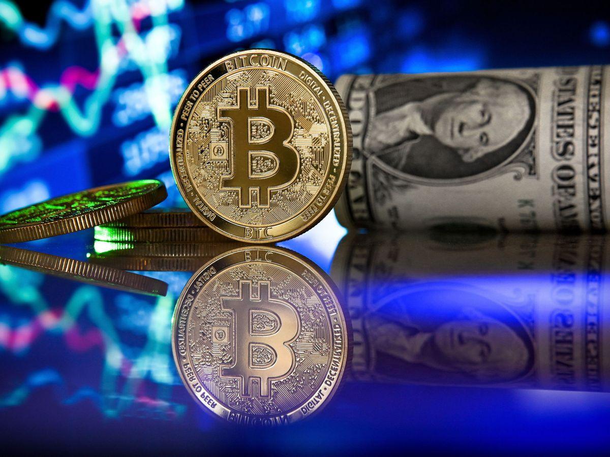 Foto: Representación del bitcóin junto a un billete de dólar. (EFE)