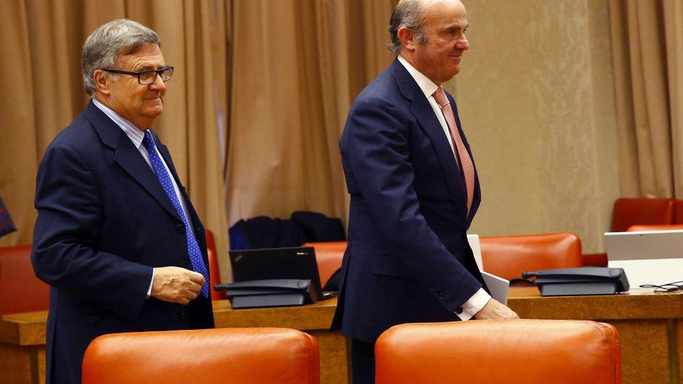 Foto: El ministro de Economía, Luis de Guindos (d), acompañado del presidente de la comisión de Economía del Congreso, Arturo García-Tizón. (EFE)