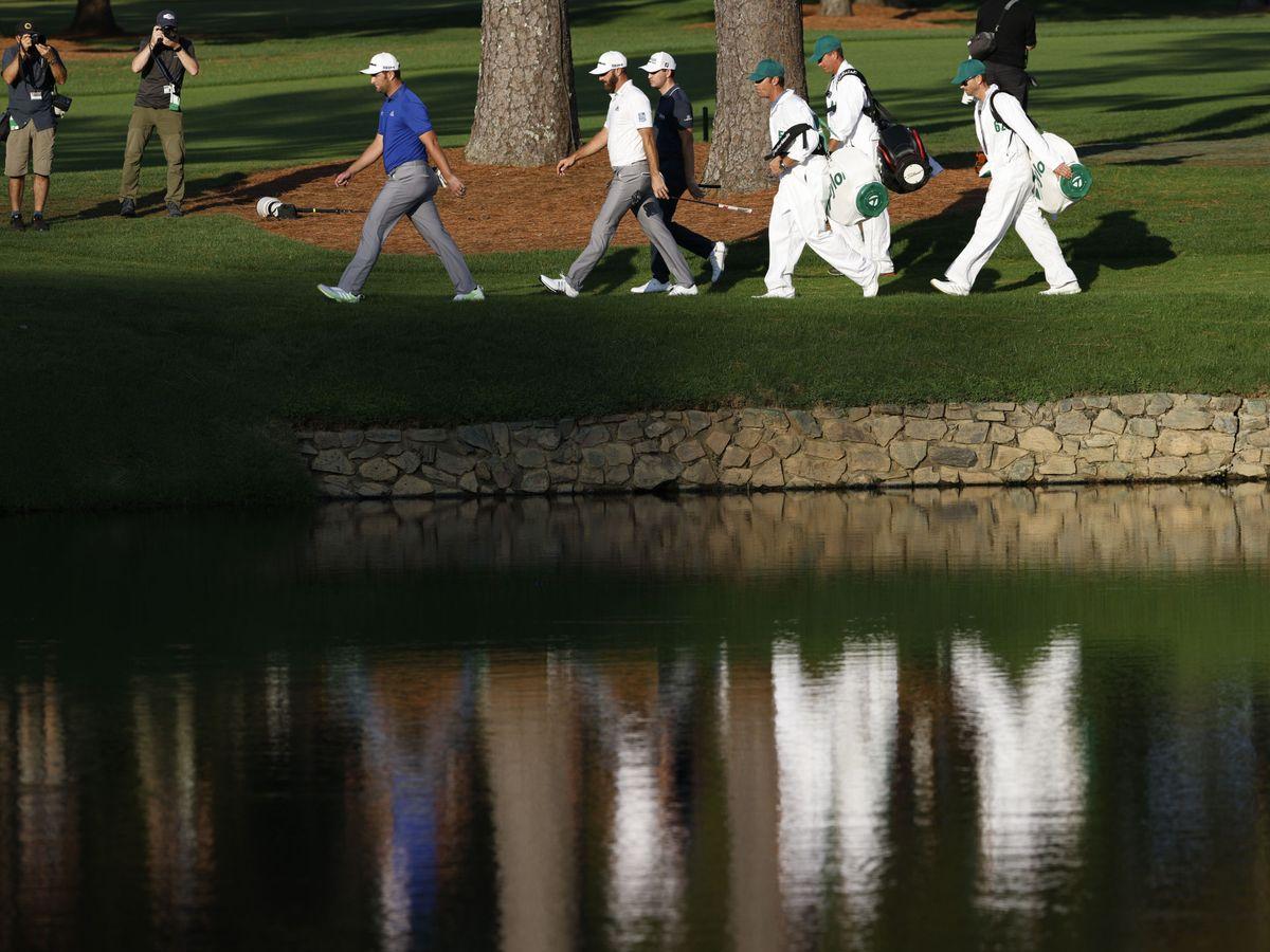 Foto: Jon Rahm, Dustin Johnson y Patrick Cantlay caminan hacia el 'tee' del hoyo 15 del Augusta National Club. (Efe)