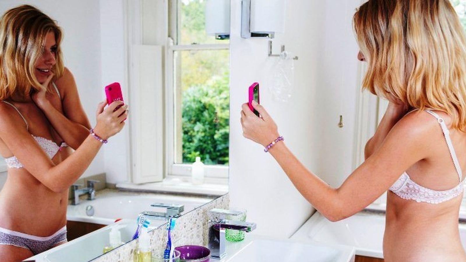 Foto: Una joven realiza una autofoto semidesnuda para enviarla a través de su móvil. (Corbis)