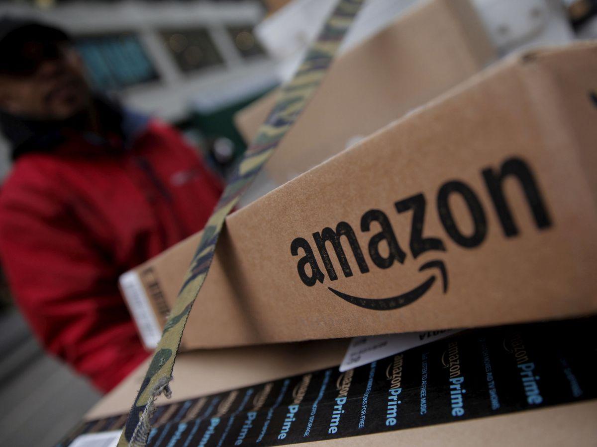 Foto: Un trabajador reparte paquetes de Amazon. (Reuters)