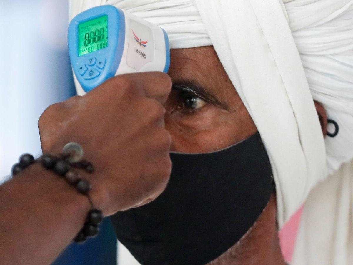Foto: Un sanitario toma la temperatura de un pasajero en una estación de tren de Mumbai, India. (Reuters)