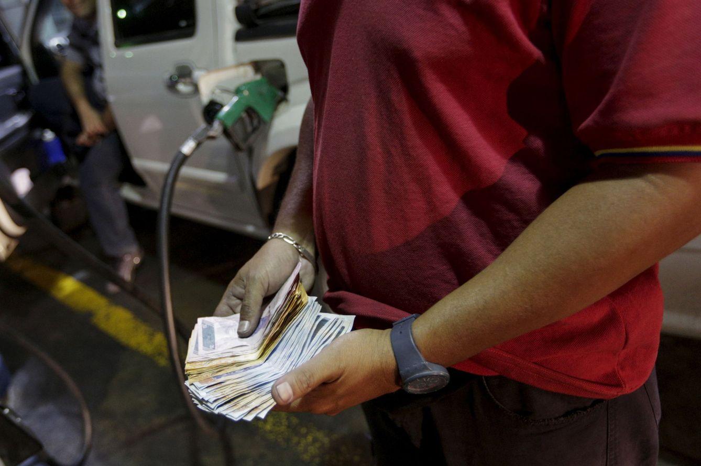 Un empleado de una gasolinera de PDVSA cuenta billetes, en Caracas, el 17 de febrero de 2016. (Reuters)