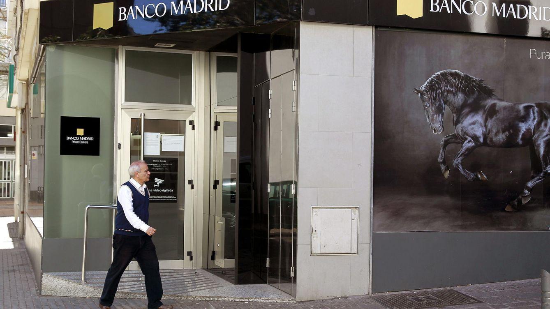 Foto: Un hombre camina cerca de una de las filiales de Banco Madrid (EFE)