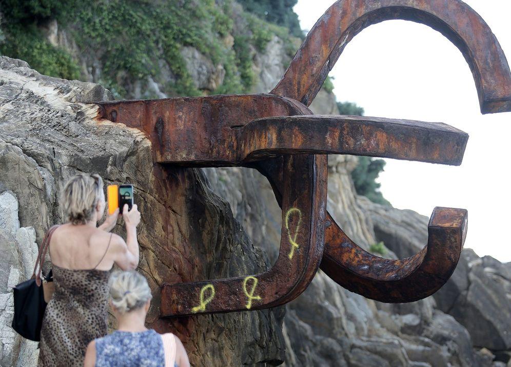 Foto: Una turista fotografía la obra de Chillida con los tres lazos amarillos pintados. (EFE)