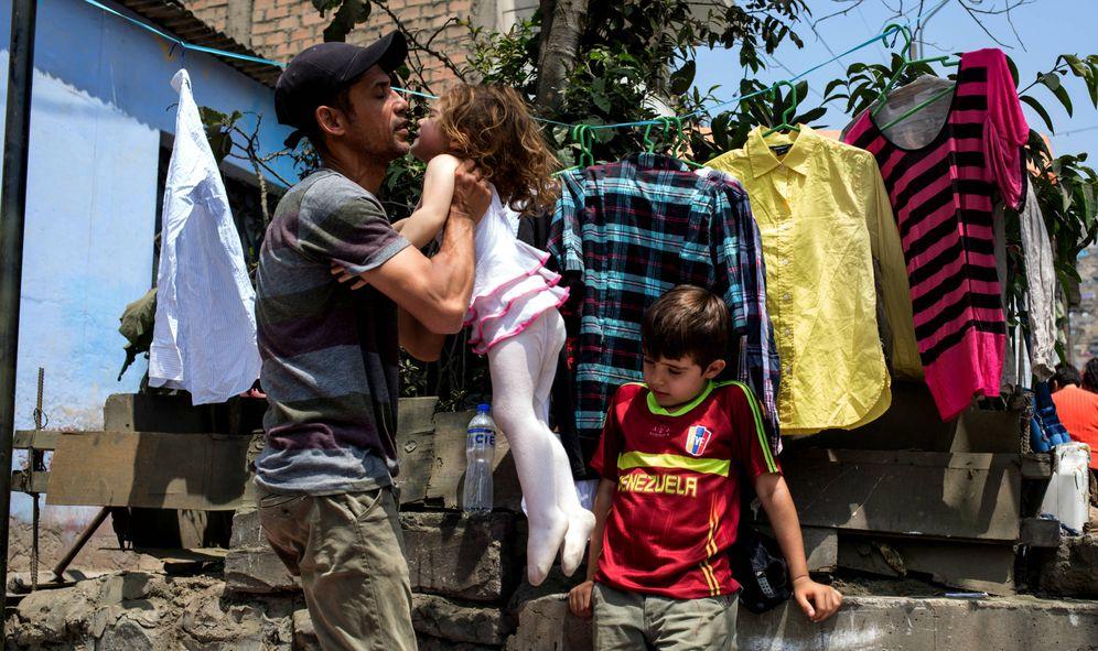 Foto: Marwin Mata con sus hijos Amelie y Jan en el pequeño espacio de venta ambulante que han establecido en Lima. (Lys Arango)