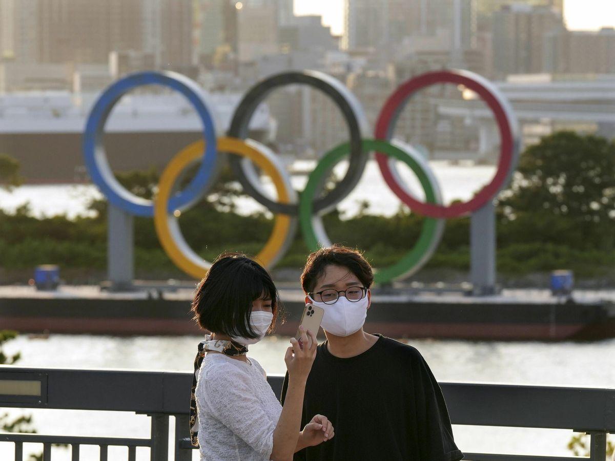 Foto: Una pareja frente a los anillos olímpicos, en la ciudad de Tokio. (Reuters)