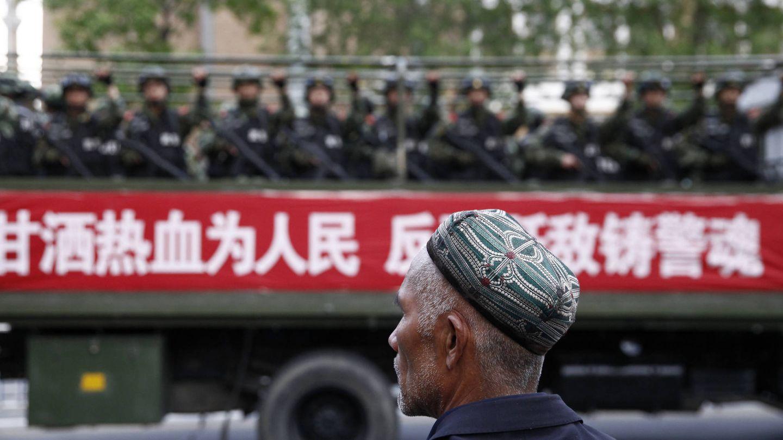 Un hombre uigur observa el despliegue de policías paramilitares durante un ejercicio antiterrorista en Urumqi, Xinjiang, en mayo de 2014. (Reuters)