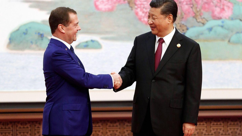 El primer ministro ruso, Dmitry Medvedev (i), estrecha la mano del presidente chino, Xi Jingping (d), durante una feria internacional de comercio. (EFE)